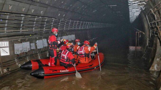 Bombeiros de bote em metrô inundado em Zhengzhou, na província chinesa de Henan Foto: STR / AFP